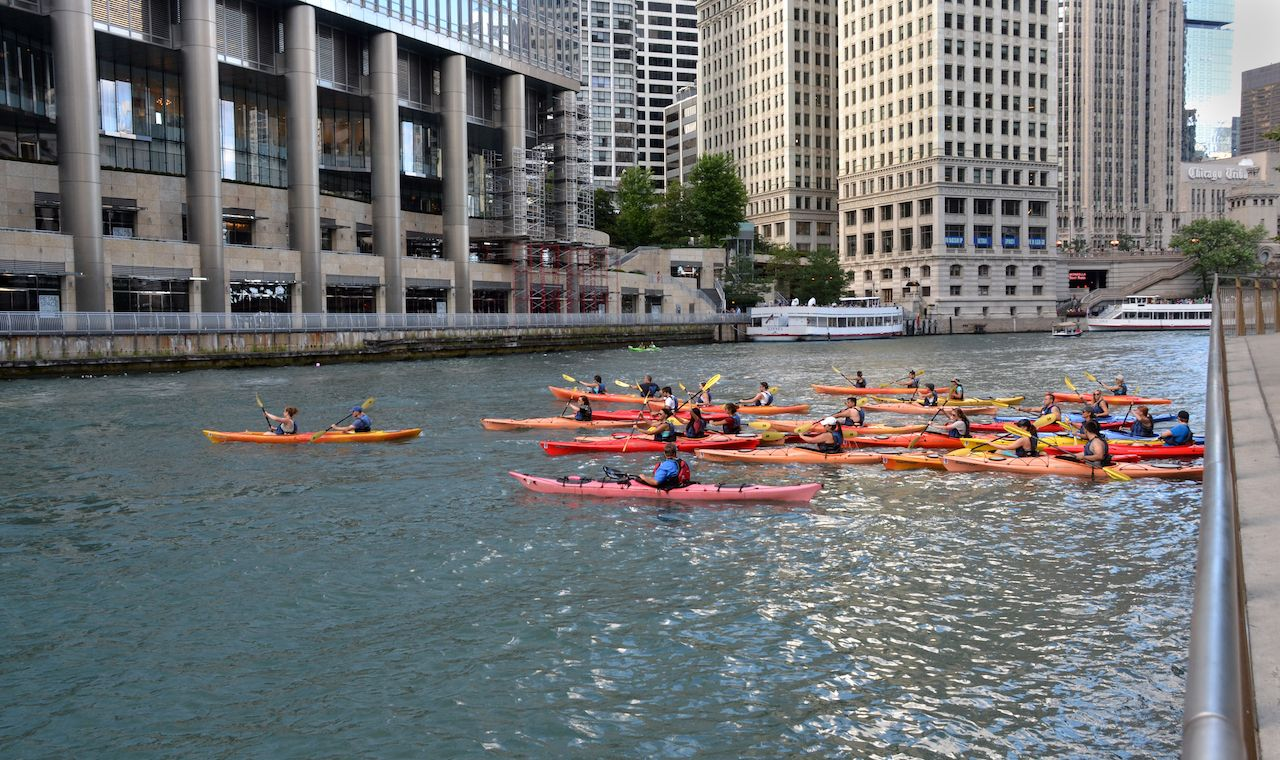 Group of summer kayakers gather on the Chicago River among the skyline