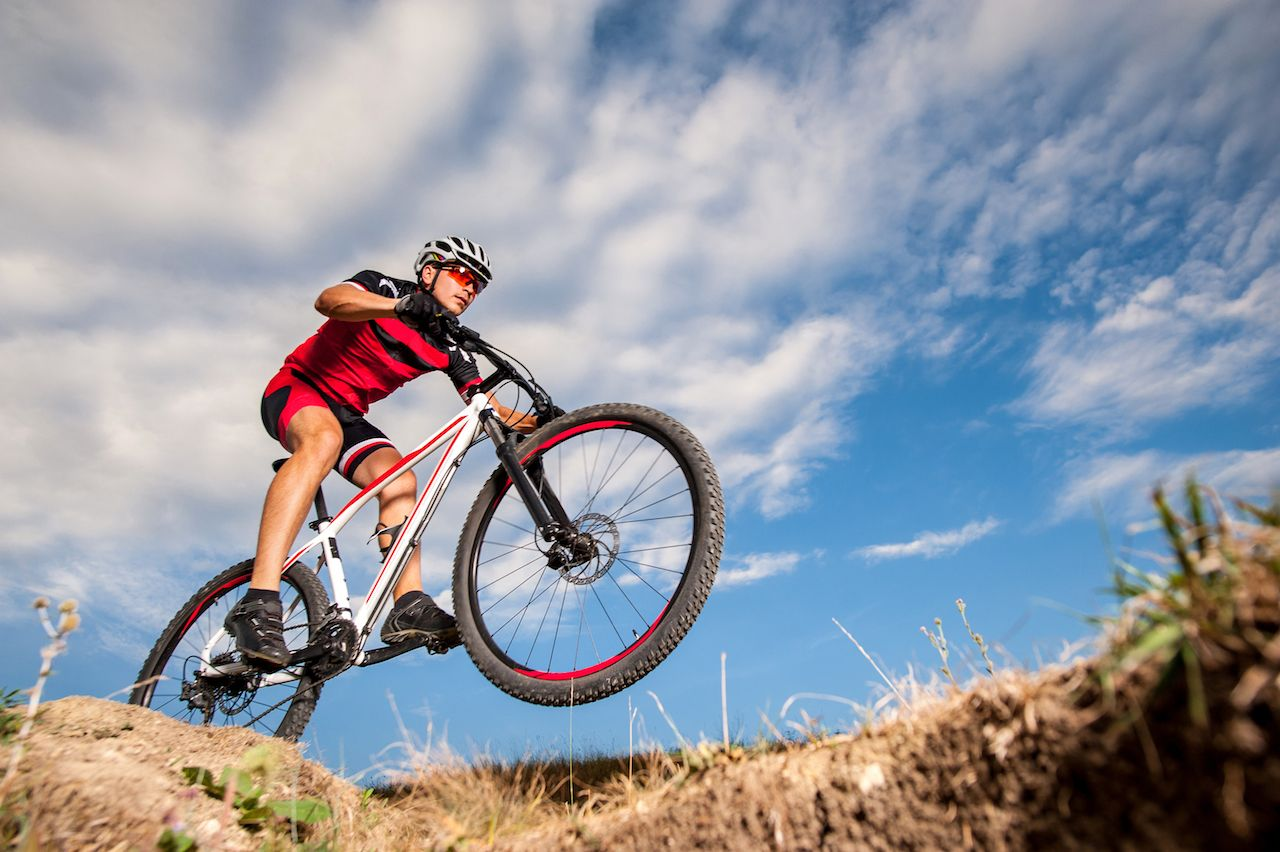 Low angle, wide angle portrait against blue sky of mountain biker going downhill
