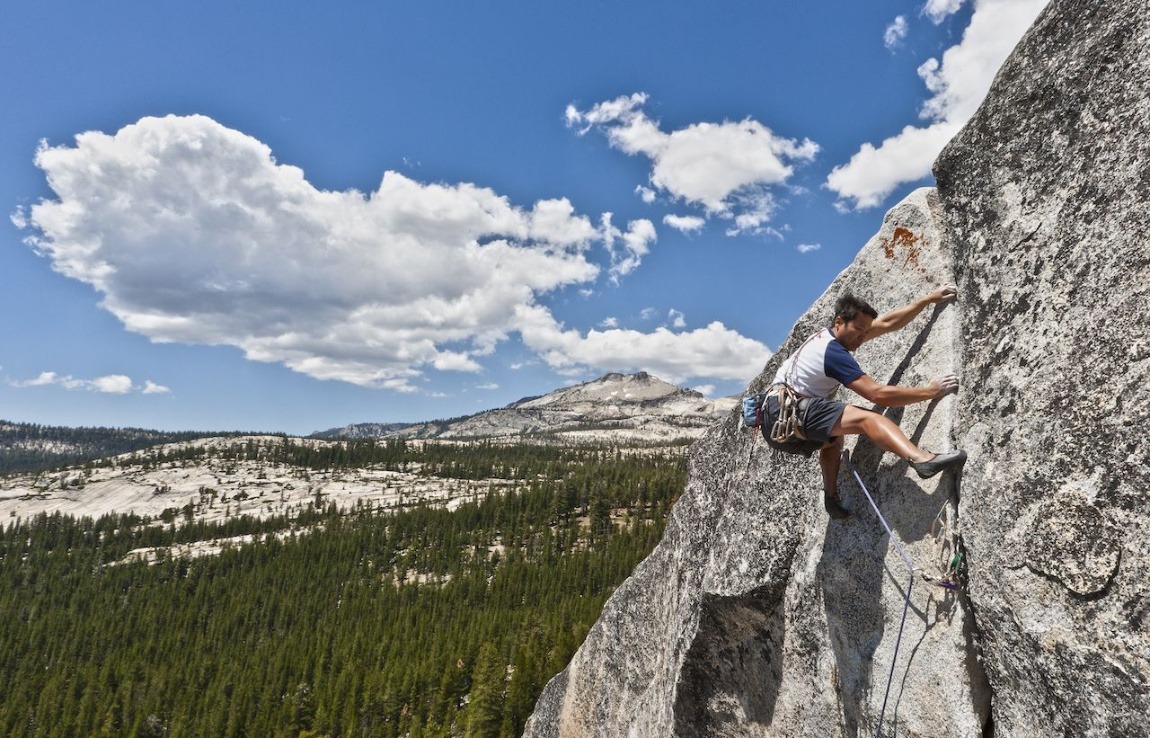 Male climber grips and scampers up a sheer rock wall in Yosemite's high Sierra Nevada mountains
