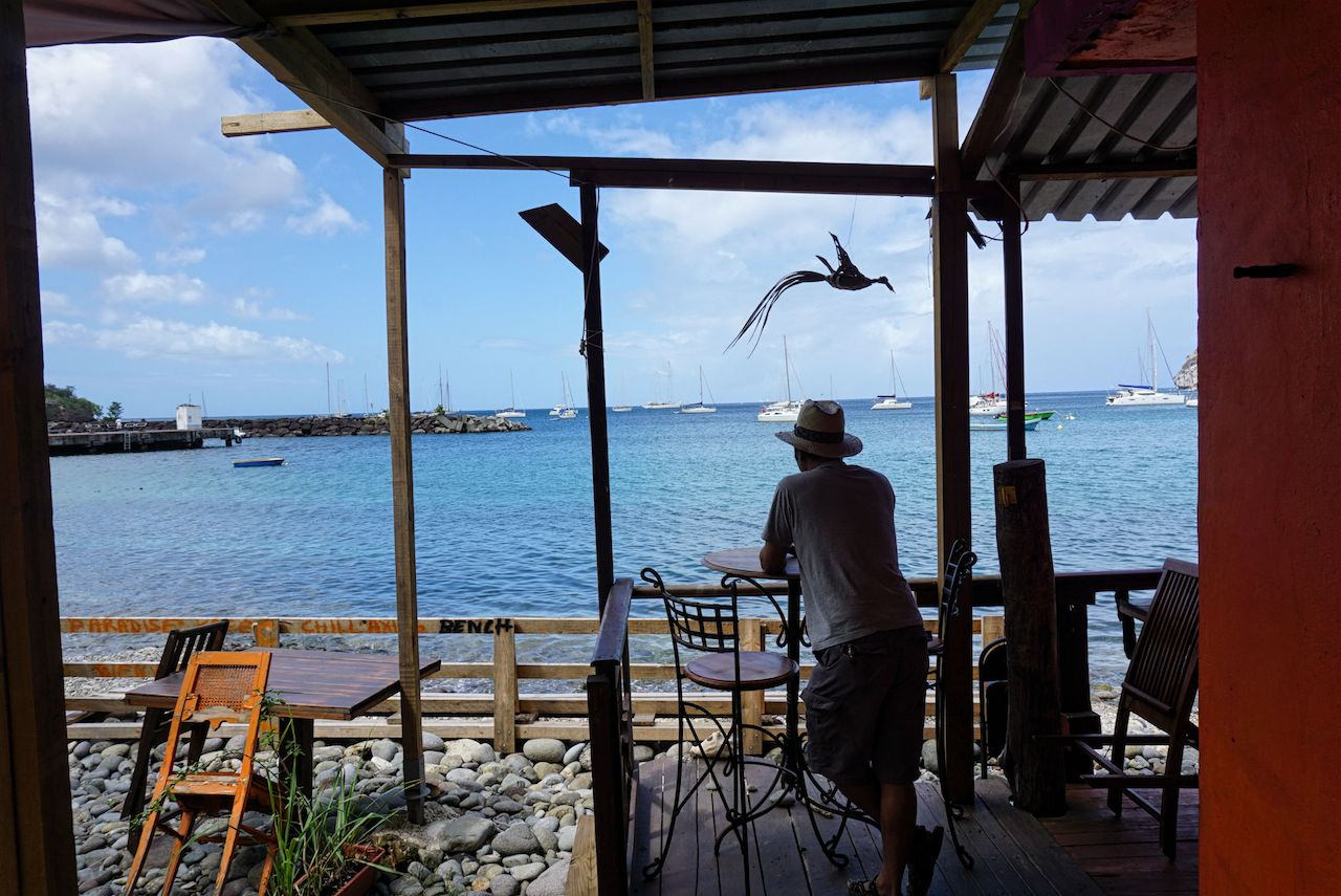Man stands outdoor restaurant Caribbean sea Guadeloupe, Deshaies