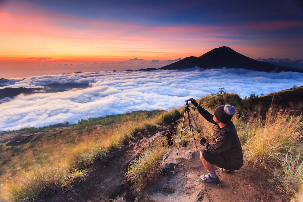 Photographer capturing beautiful sunrise using tripod taken from Batur mountain Bali Indonesia