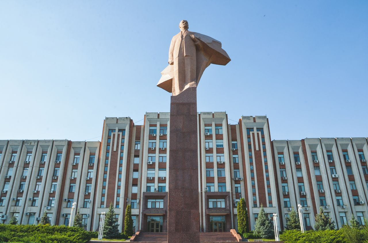 Statue of Lenin, Brutalist architecture, and flag with Soviet emblems in Tiraspol