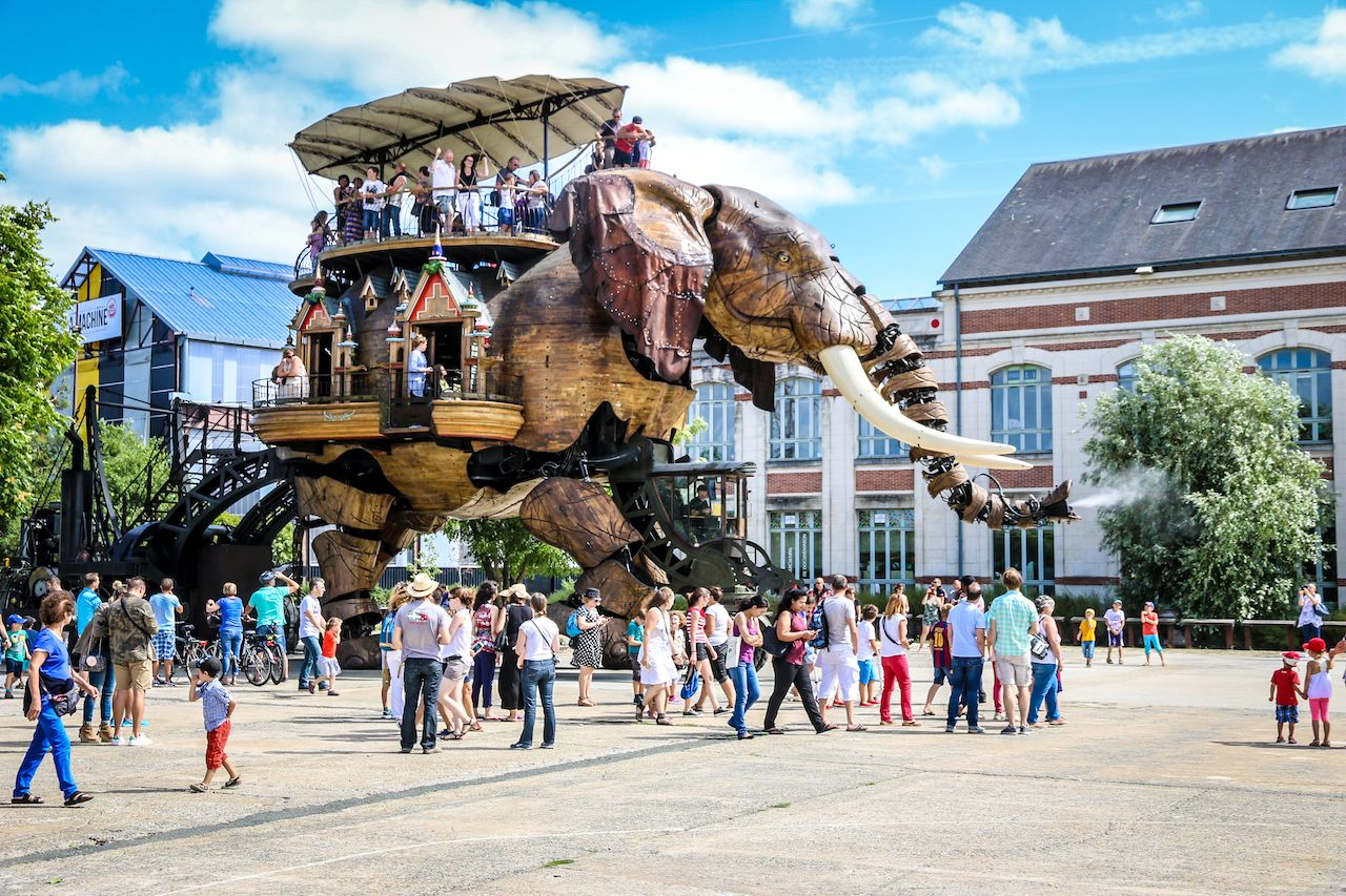 The Great Elephant of the Machines de l'Ile carrying passengers in city square in Nantes, France