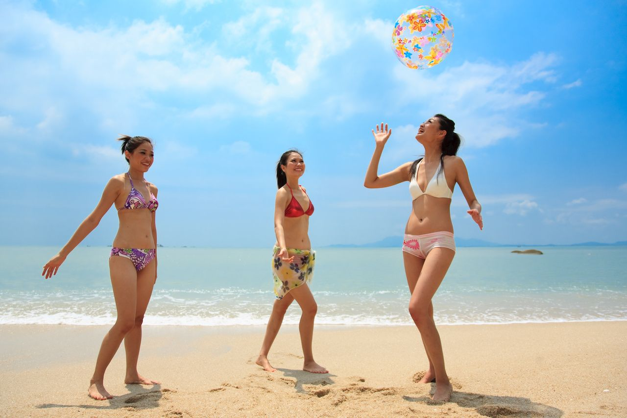 Three beautiful young woman playing with an inflatable ball near the ocean