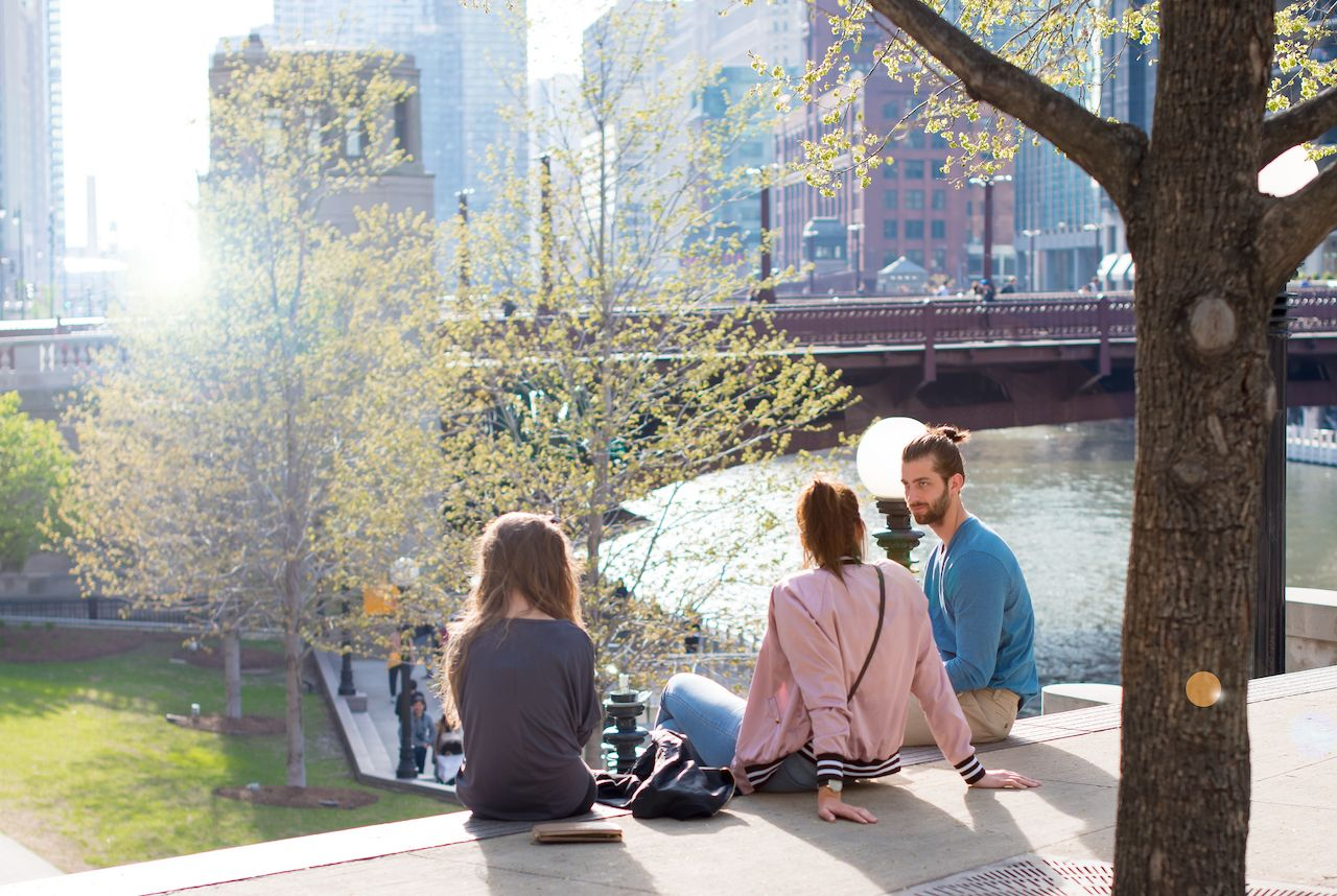 Three young friends enjoy a moment of hanging out together along Chicago's Riverwalk