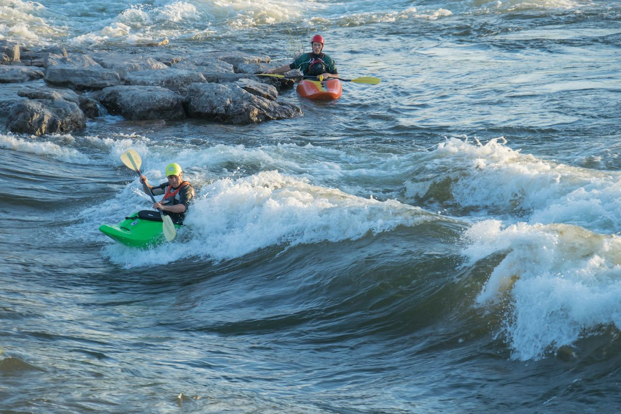 Two men kayaking Brennan's wave in Missoula, Montana
