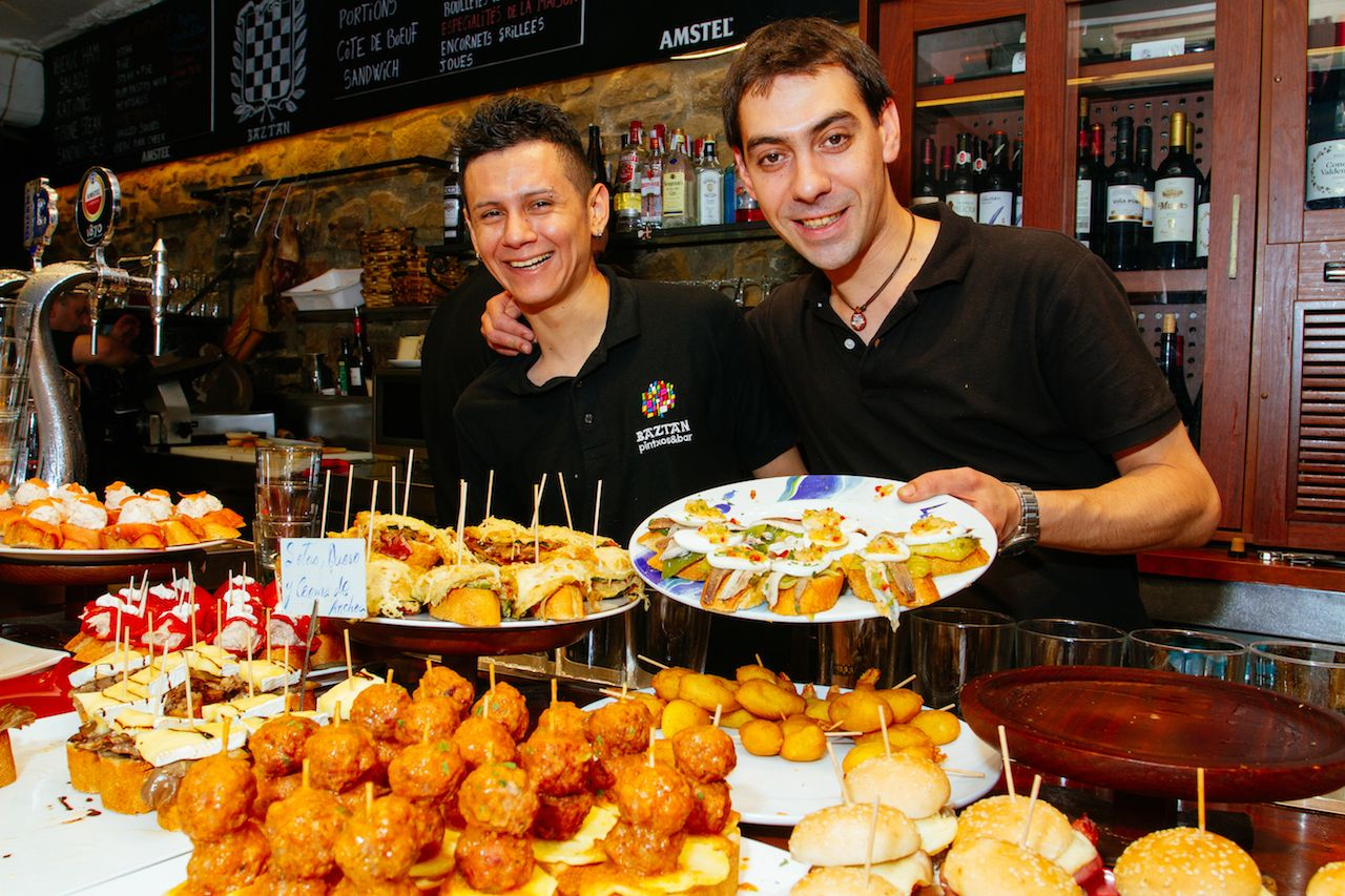 Two waiters show the tapas of the bar of a bar of San Sebastian