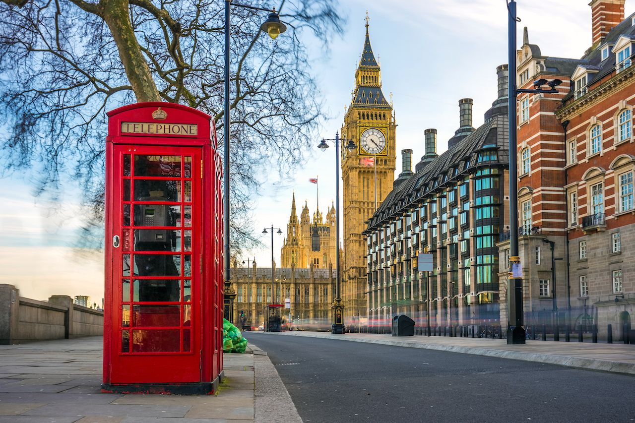 british old red telephone box with the Big Ben at background in the center of London