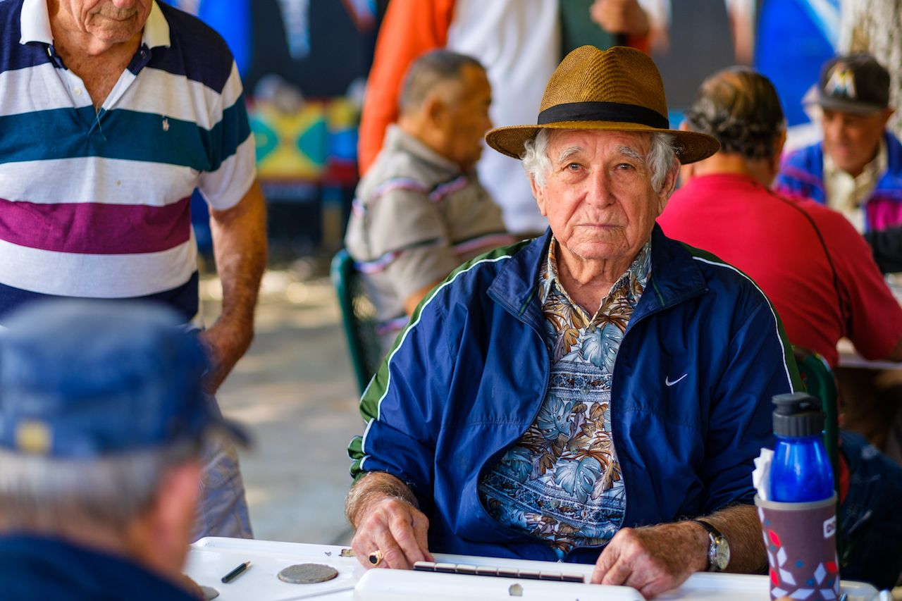 elderly man plays the domino game in the historic Domino Park in popular Little Havana