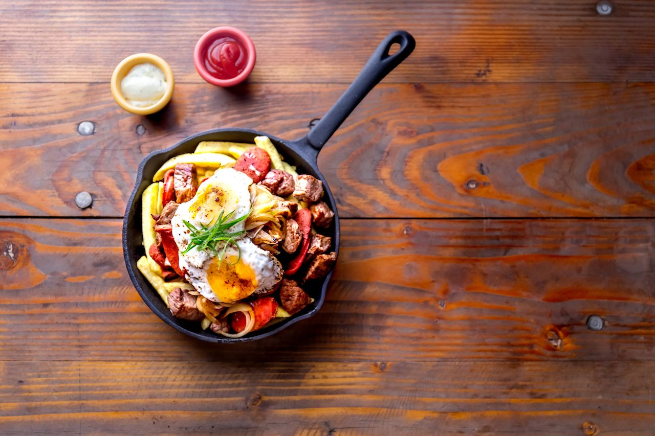 french fries topped with sliced ​​beef, tipical sausages chorrisos, fried onion and eggs served in iron cast pan with sauces