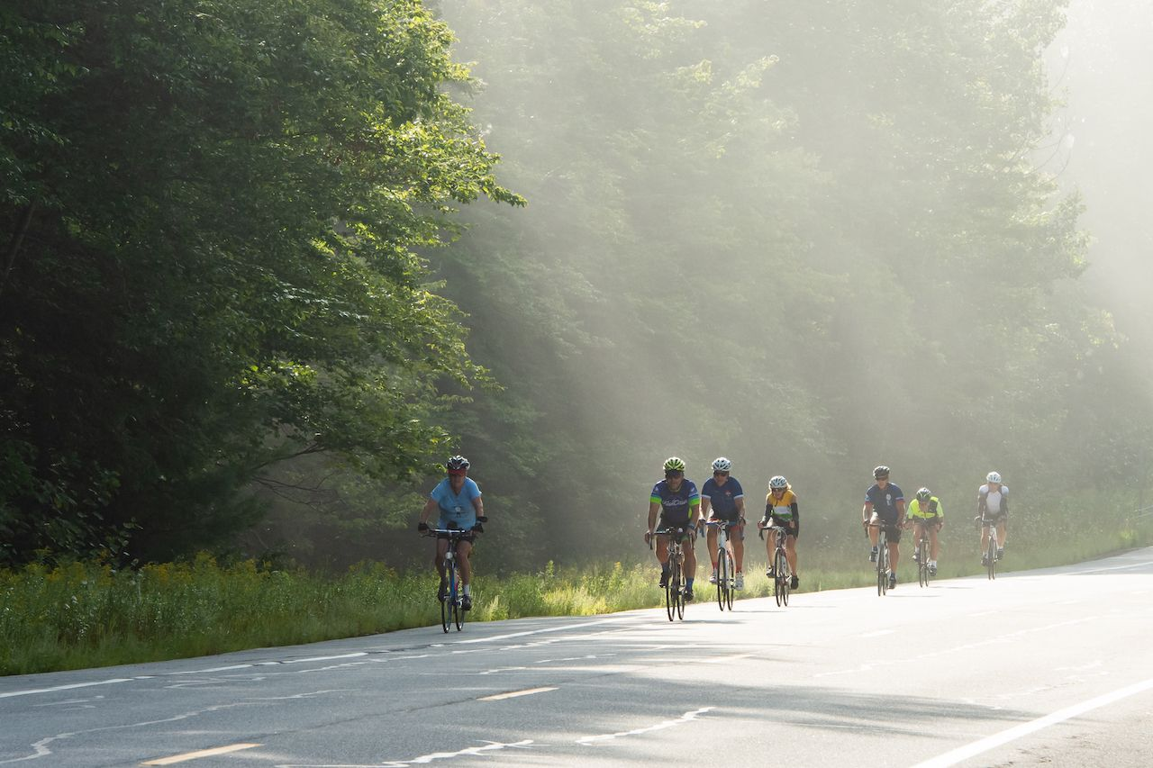 A group of bicycle riders riding through an early morning foggy morning ride through the Adirondack Mountains wilderness