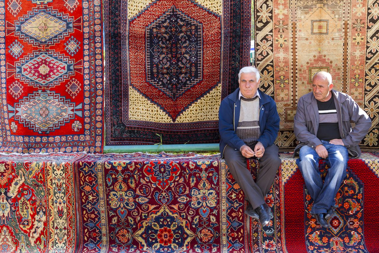 Armenian men sit and relax on carpets at the Vernissage Market in Yerevan, Armenia