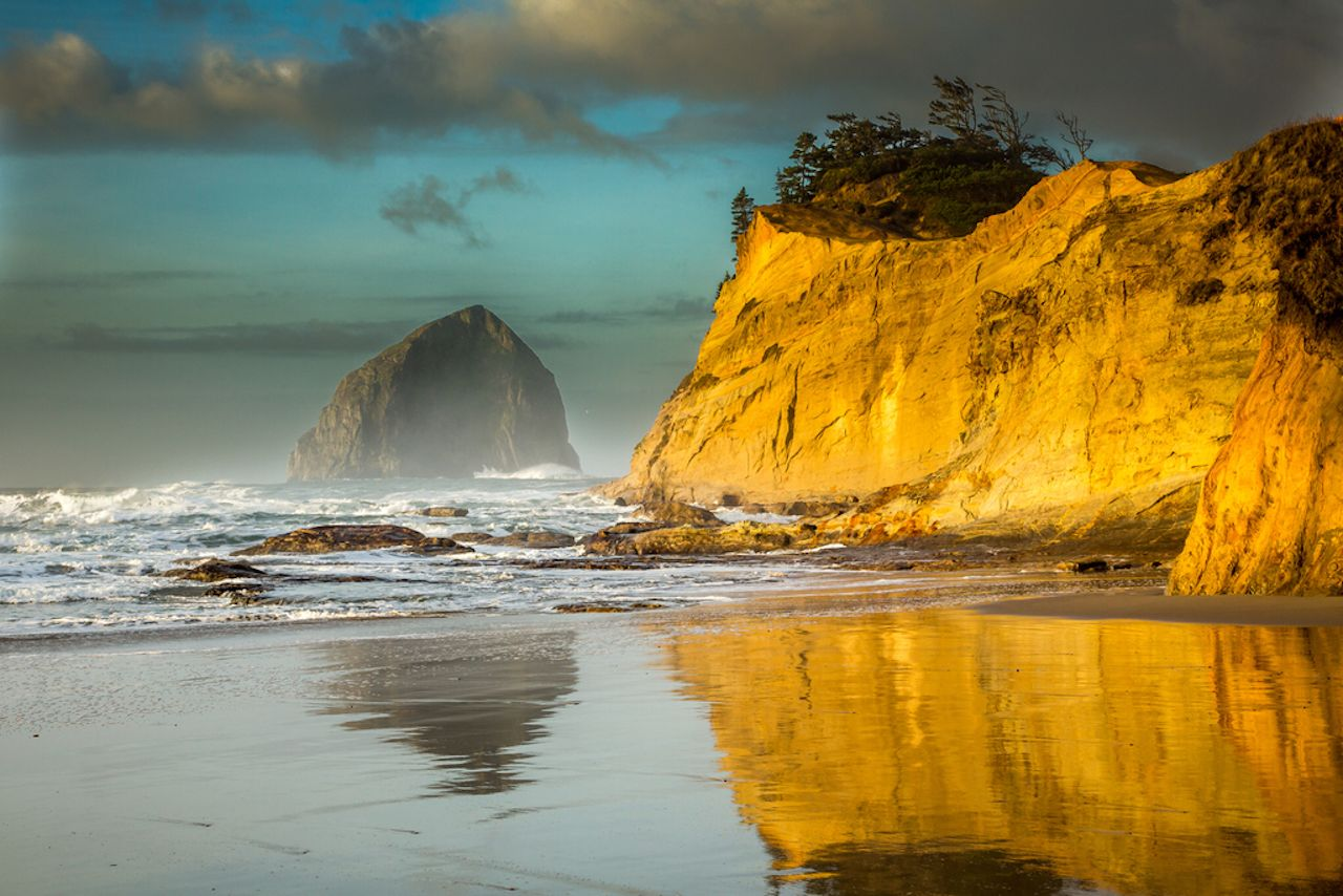 Cape Kiwanda and Haystact Rock reflected the the wet sand on the beach at Pacific city on the Oregon coast