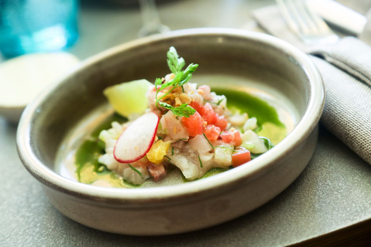 Ceviche fish served with green sauce and lime