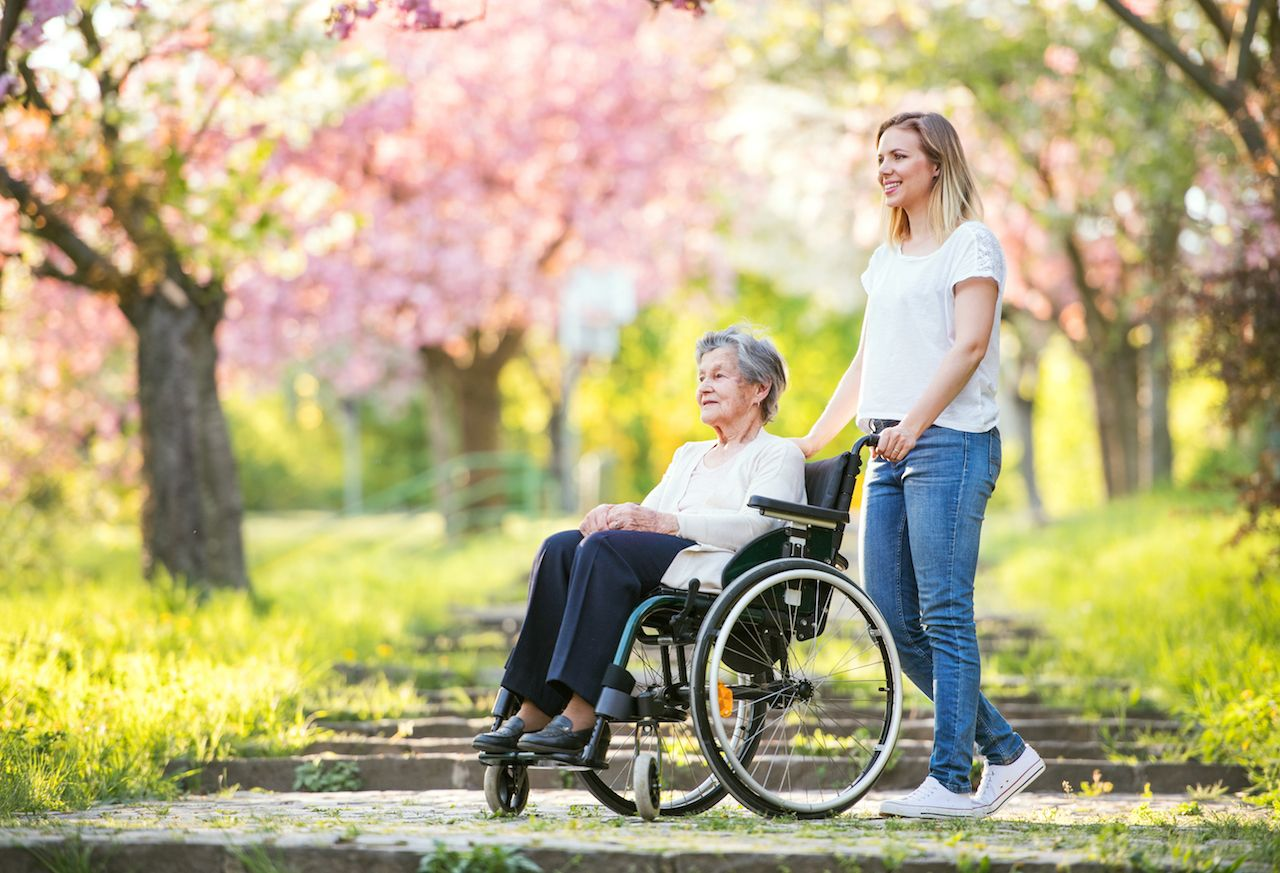 Elderly grandmother in wheelchair with granddaughter in spring nature