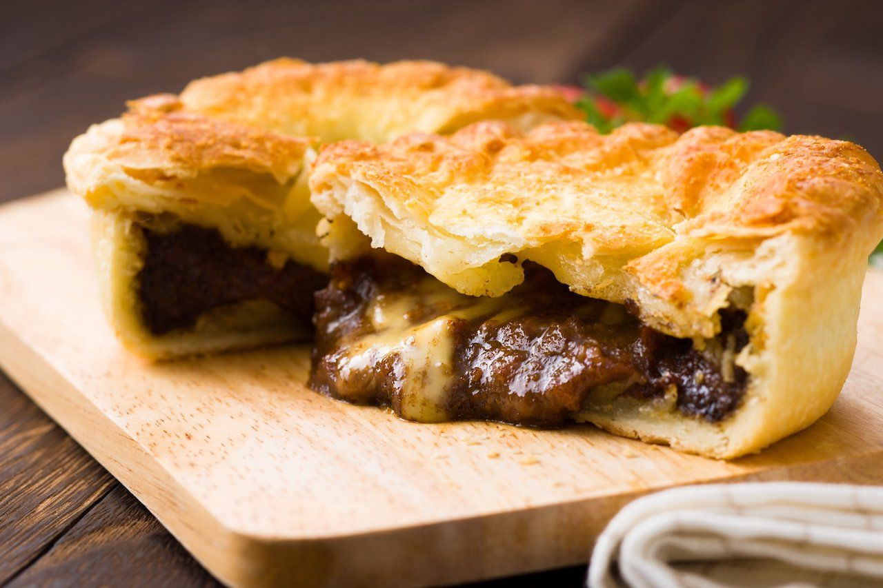 Flaky, juicy meat pie on a wooden cutting board