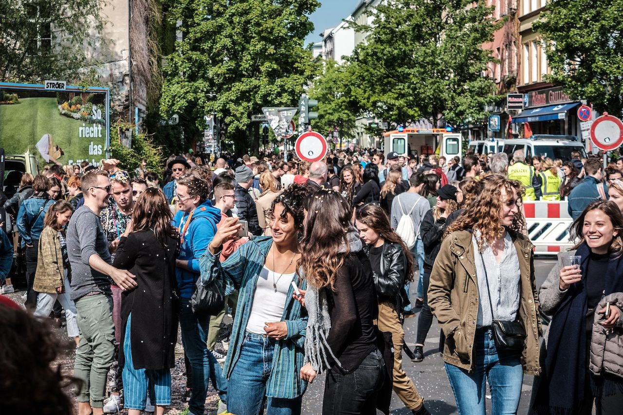 Happy young people on crowded street celebrating labor day in Berlin, Kreuzebrg
