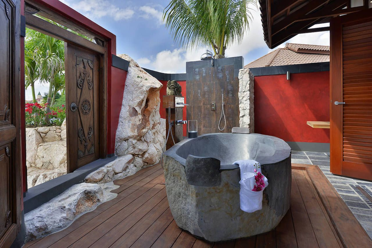 Luxurious outdoor bath and shower in stone with red walls, intricate wooden doors, and views of Curacao