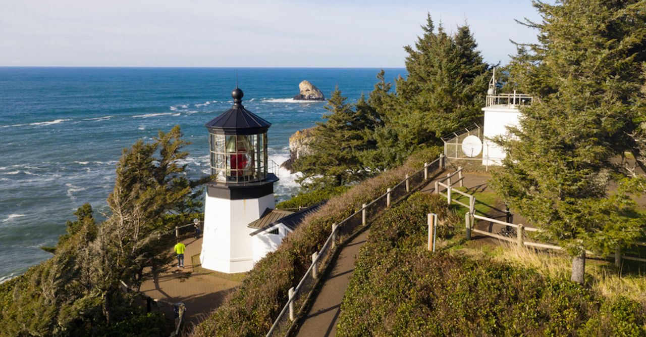 Pacific Ocean waves crash against high bluffs below Cape Mears Lighthouse