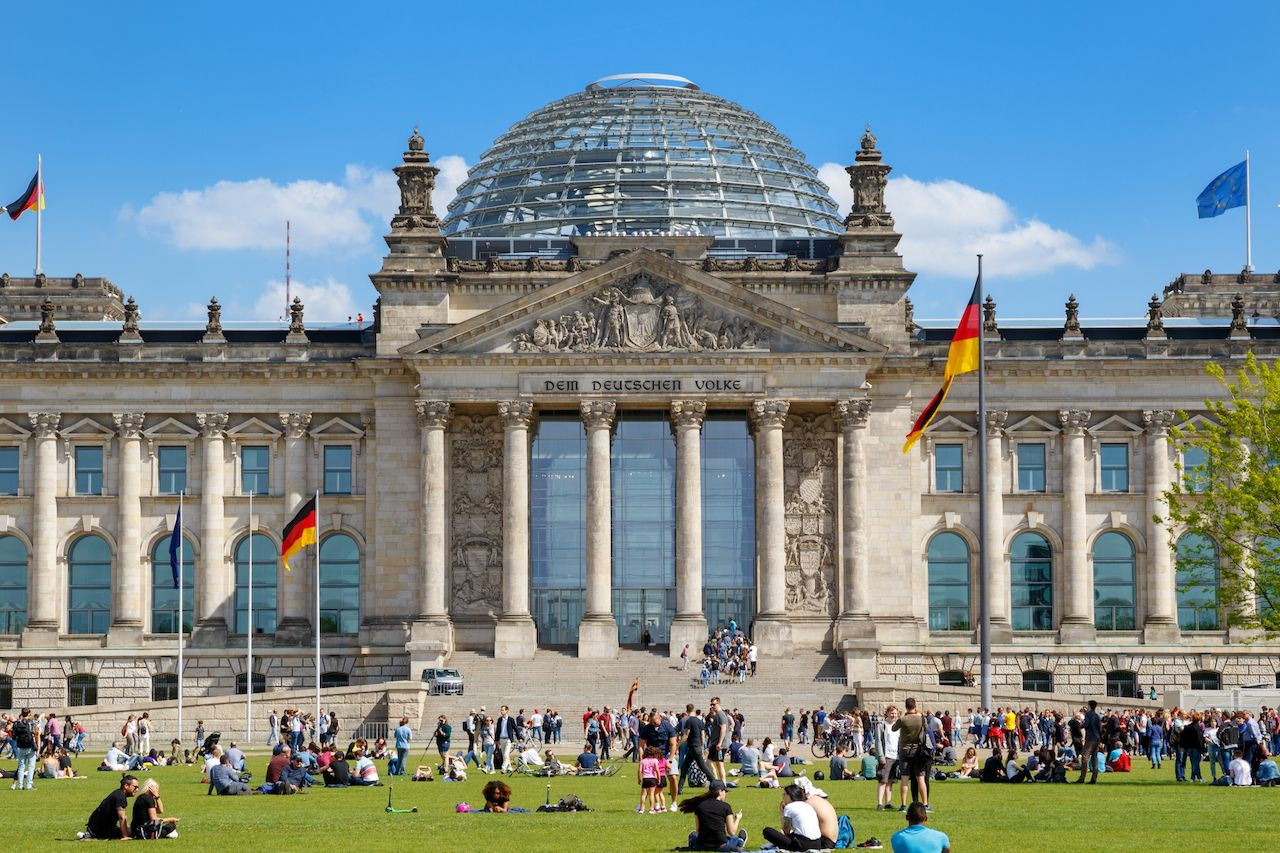 People relaxing on the grass in front of the Reichstag building
