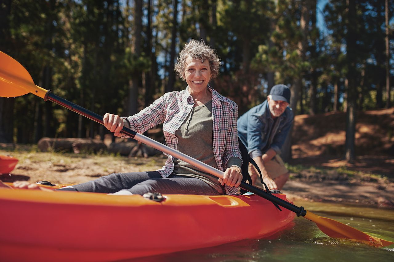 Portrait of happy senior woman in a kayak holding paddles
