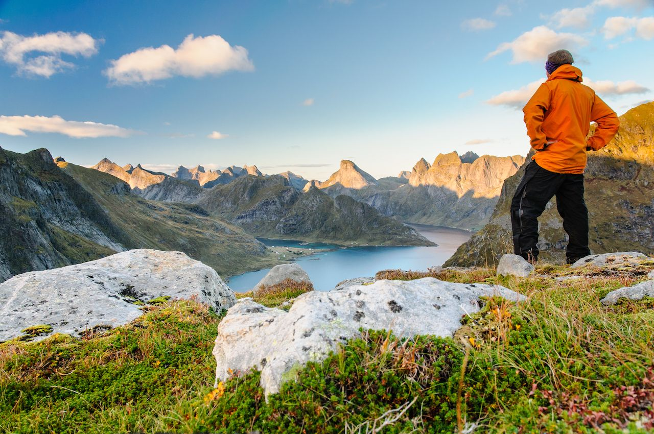 Relaxed hiker enjoys stunning views on fjords and mountain peaks of Lofoten islands, Norway