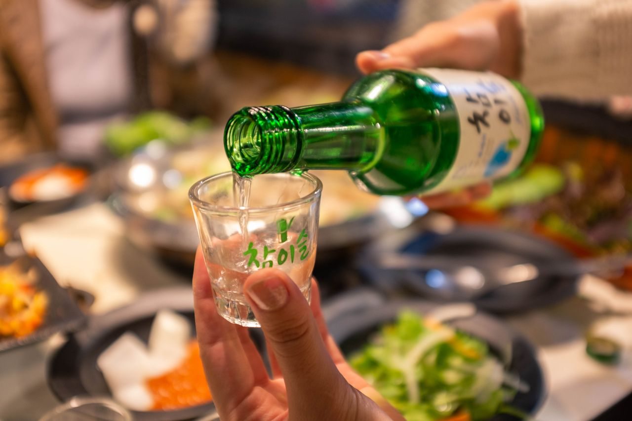 Soju being poured into a glass