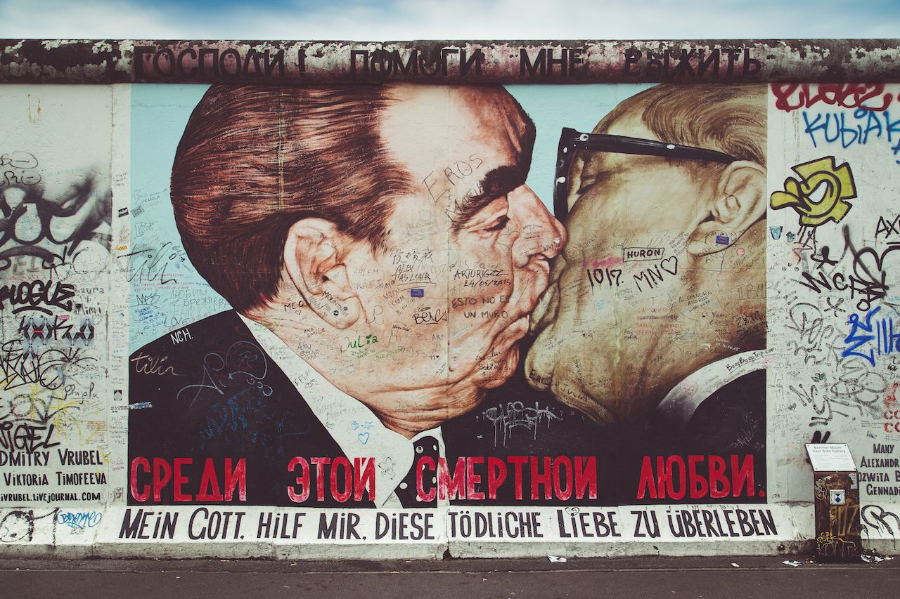 Street art graffiti painting 'The Kiss' by Dmitri Vrubel at famous East Side Gallery, the Berlin Wall, Berlin