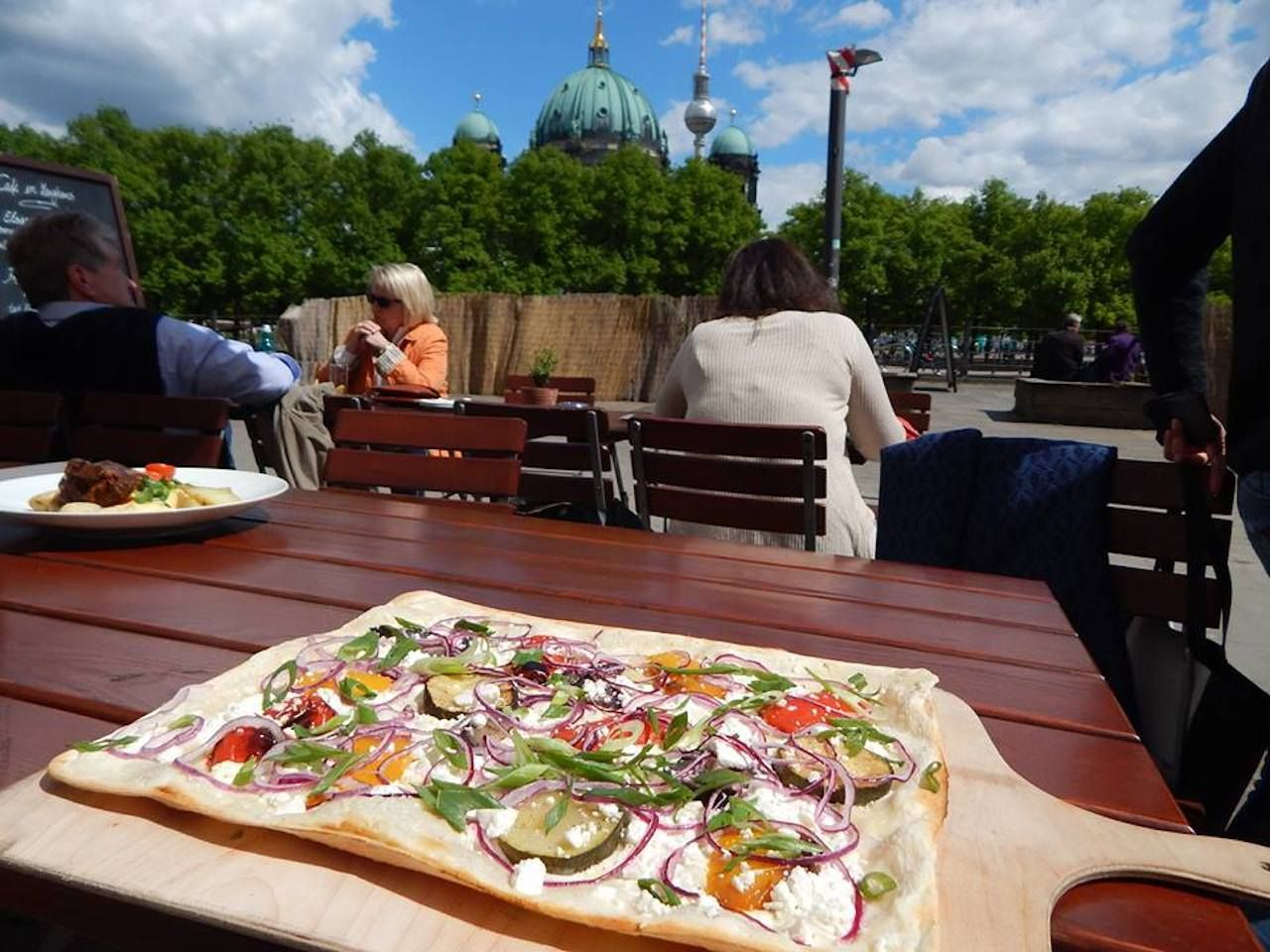 Table with flatbread pizza in front of Berlin landmark