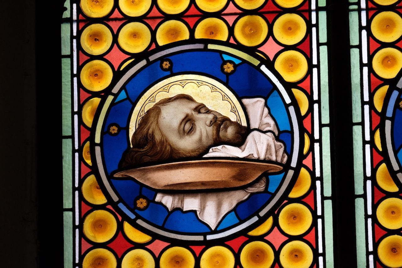 The head of Saint John the Baptist, stained glass window in Basilica of San Silvestro in Capite in Rome, Italy