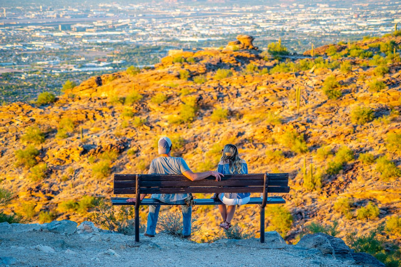 Two people watching the sun go down over Phoenix, Arizona from Dobbins Lookout on South Mountain