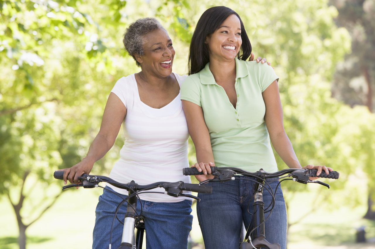 Two women on outdoors bikes smiling