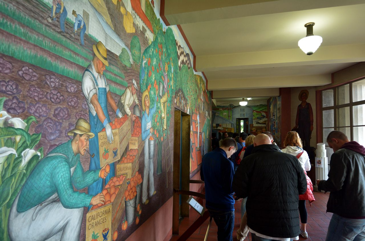 Visitors and mural at Coit Tower lobby in San Francisco