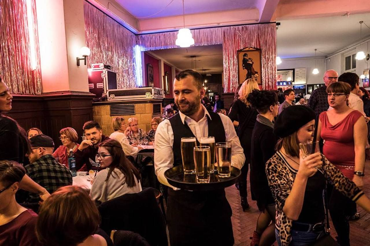 Waiter carrying beers in a Berlin ball house