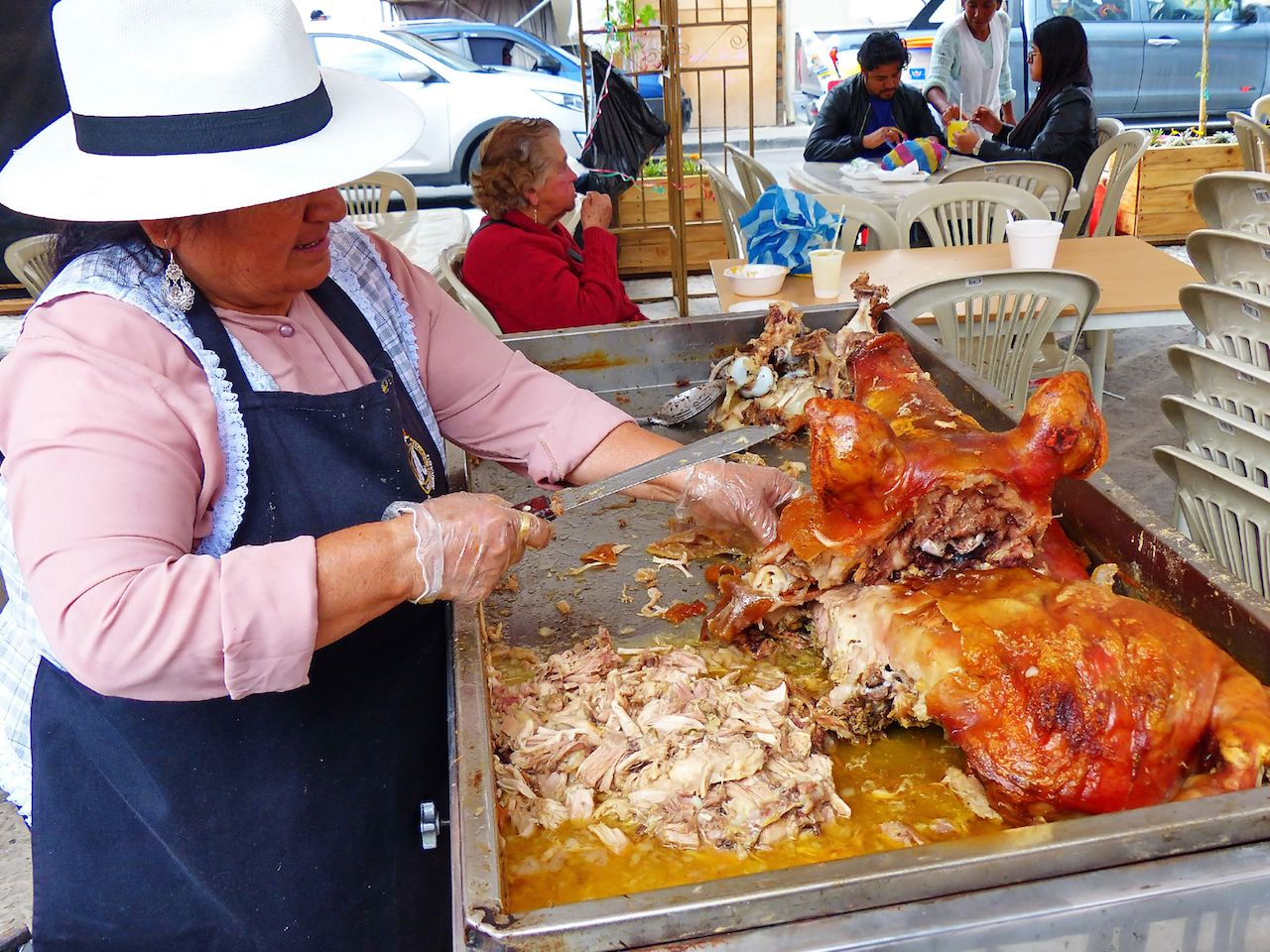 Woman selling sellling roasted pig in an Ecuadorian plaza