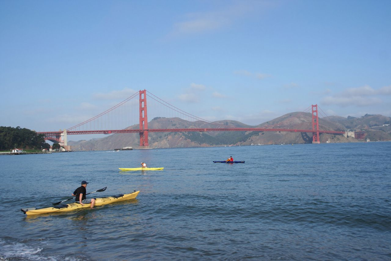 three men kayaking by the Golden Gate bridge San Francisco bay