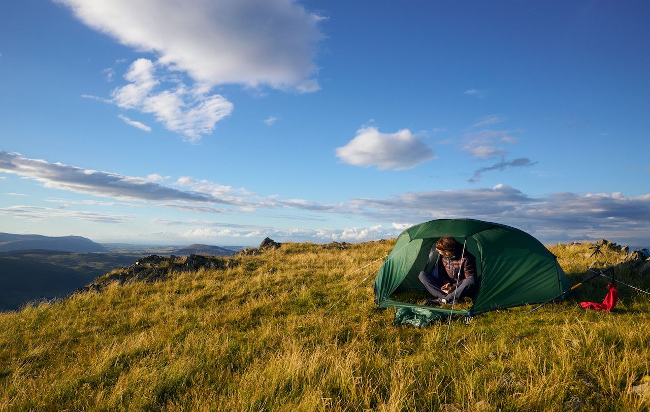 A hiker camping on the mountain summit of Place Fell in the Lake District at sunset