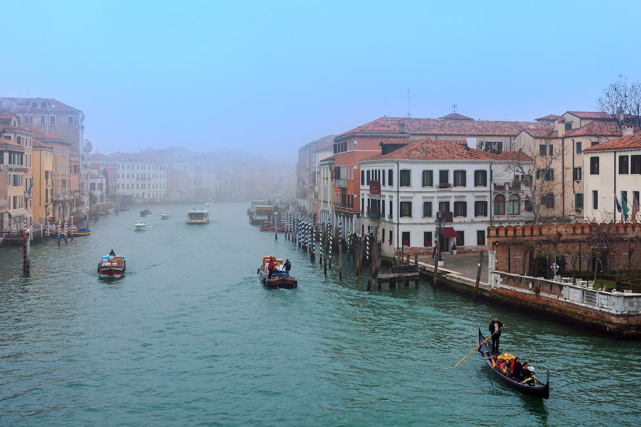 Boats and gondola on misty morning on Grand Canal in Venice