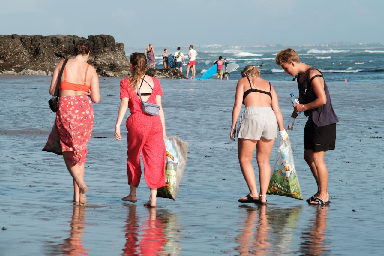 People are picking up trash on the beach for 2019 Beach Clean Up event in Canggu