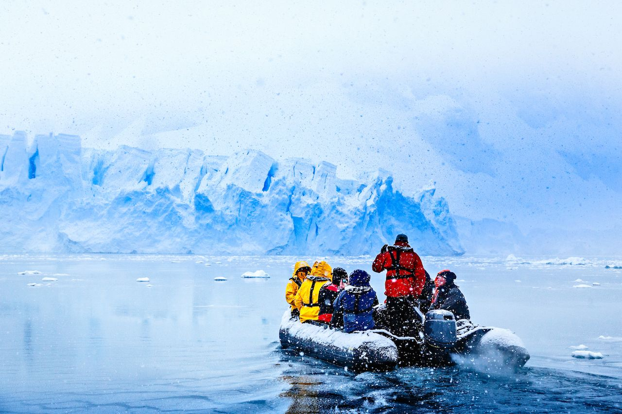 Snowfall over the boat with tourists driving towards a huge blue glacier wall, near Almirante Brown, Antarctic peninsula