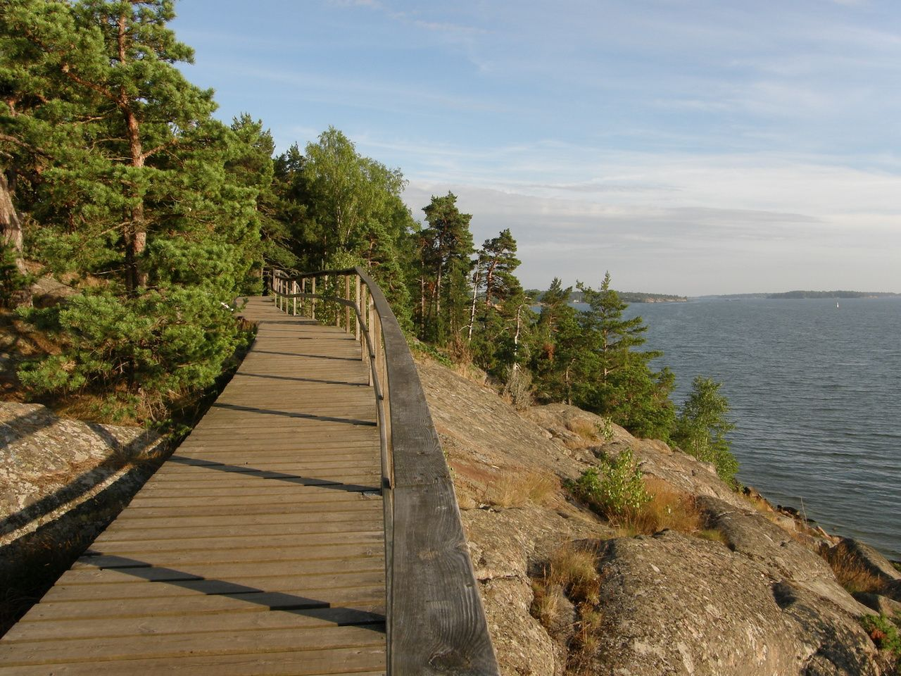 Wooden pedestrian path in pink granite rocks of Mariehamn, Aland archipelago, Finland
