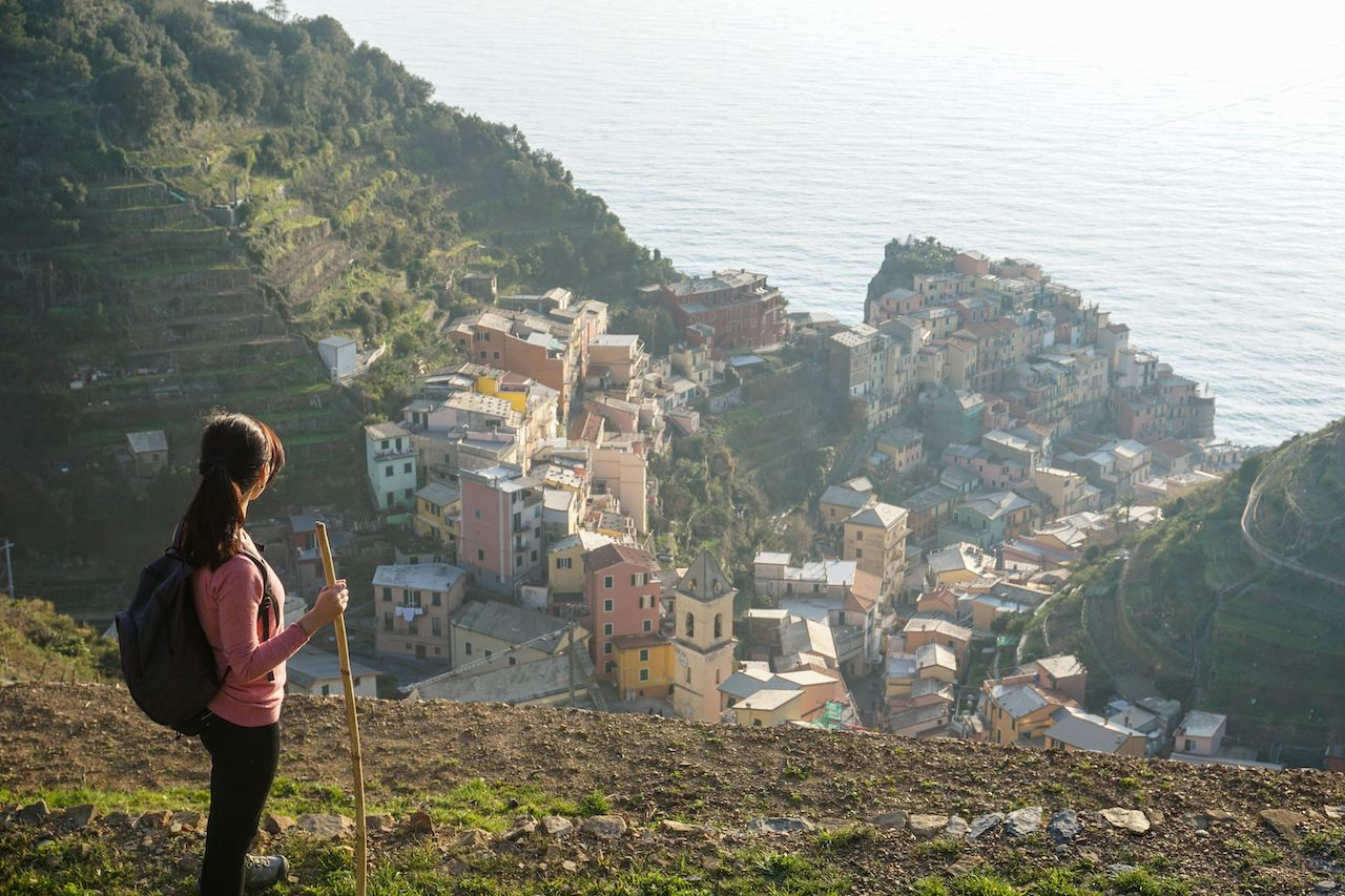 Young hiker looking at Manarola village, Cinque Terre National Park, Liguria, La Spezia, Italy