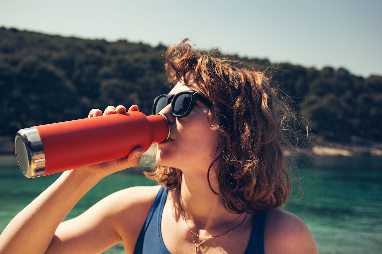 girl drinking from a steel water bottle at the beach