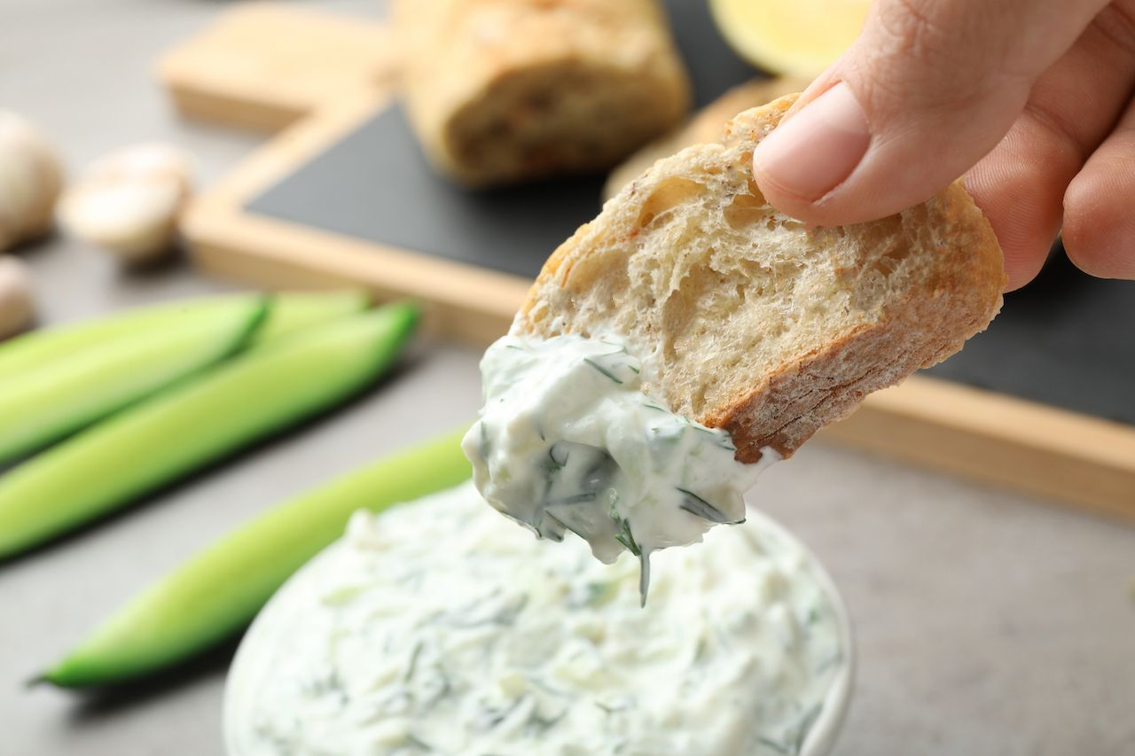 Bread dipped in tzatziki