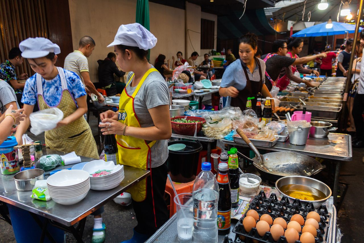 Cooks preparing fast and cheap meals in a big food stall on the street in Silom district