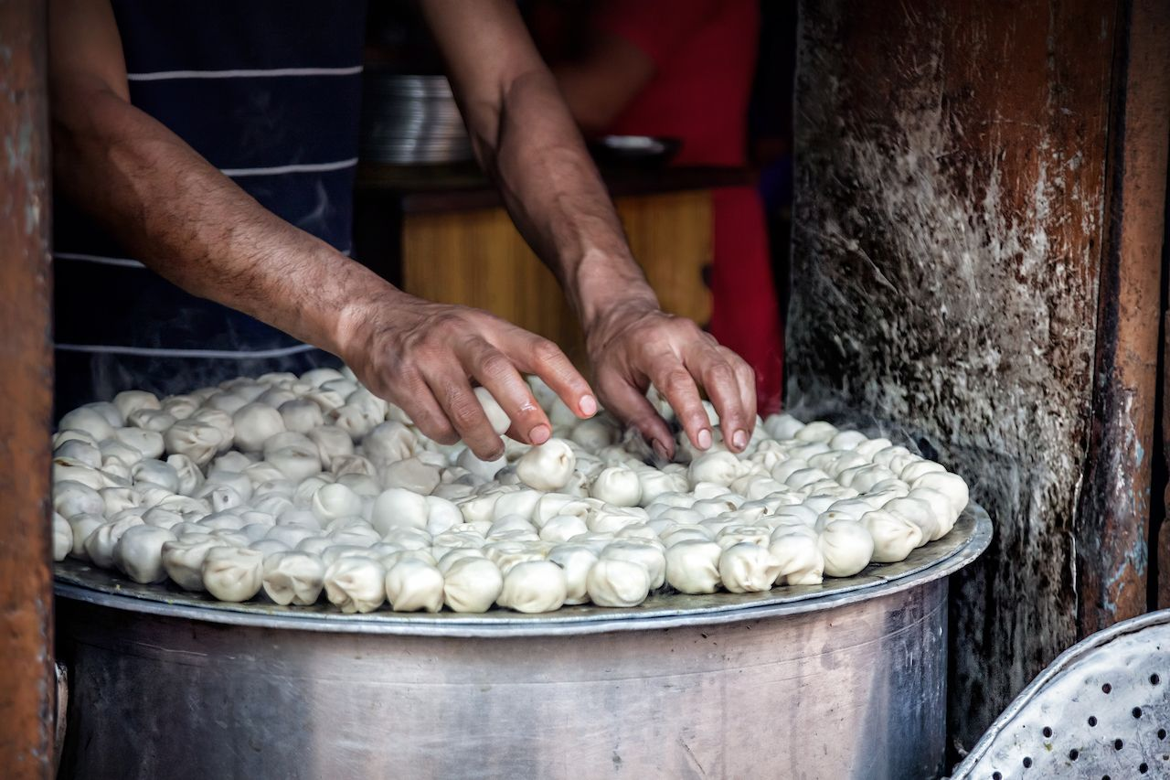 Man cooking steamed traditional Nepalese momos in the street kitchen