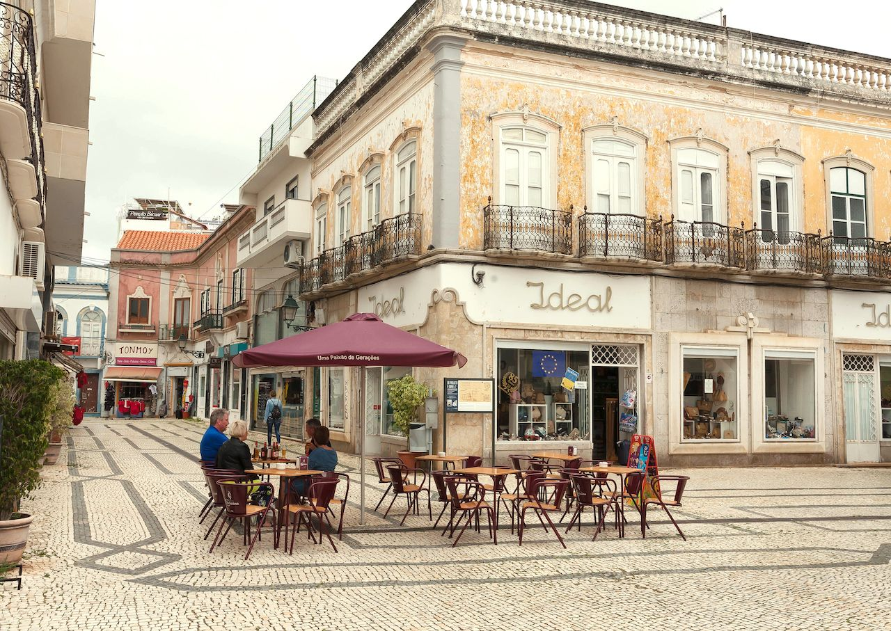 People drinking at outdoor cafe on historical street of Algarve
