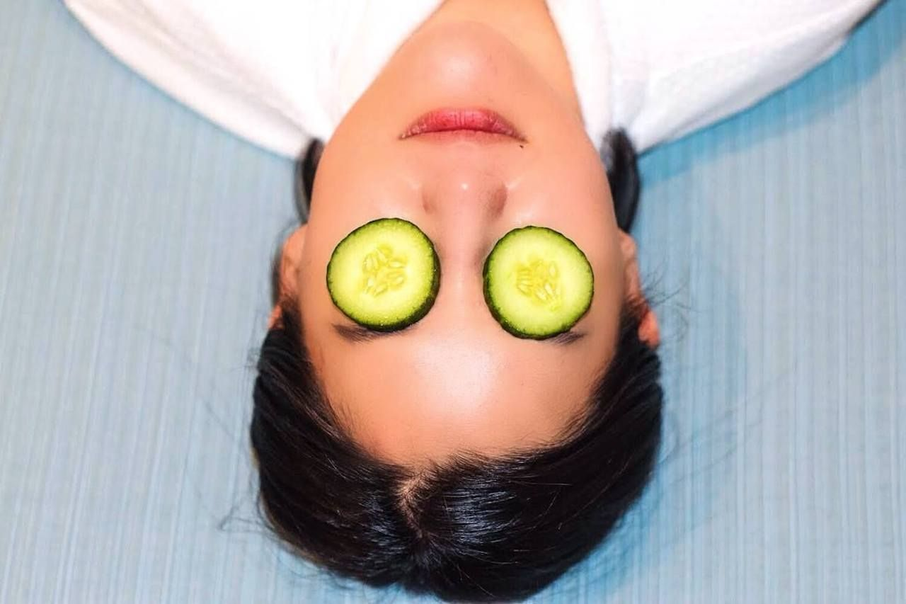 Person with cucumbers on eyes