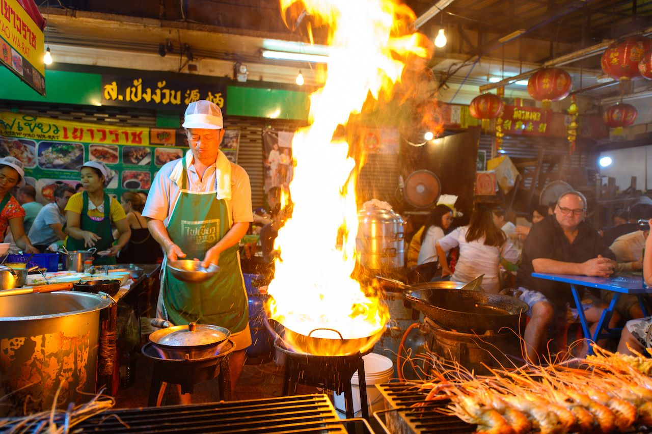 Street food chef cooking with fire at Yaowarat road in Bangkok