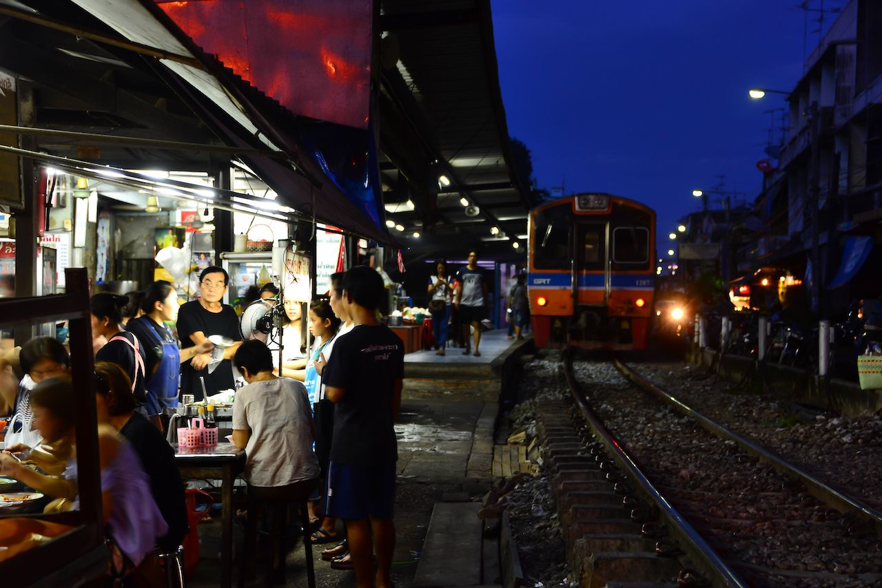 Train is arriving to local street food market at talat phlu station